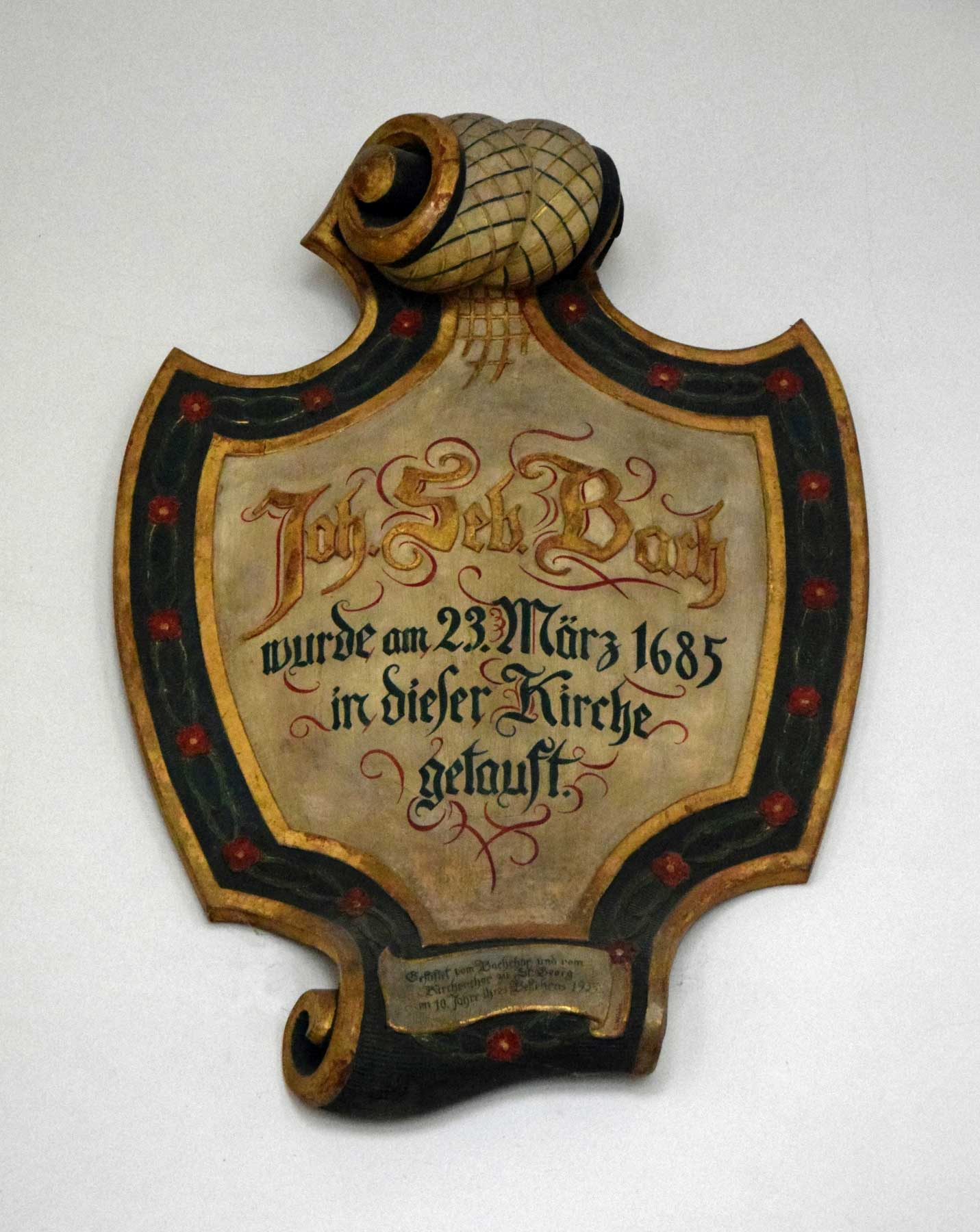 A wooden memorial plate above the entrance portal of the Georgenkirche in Eisenach, commemorating Bach's baptism according to the Julian calendar.